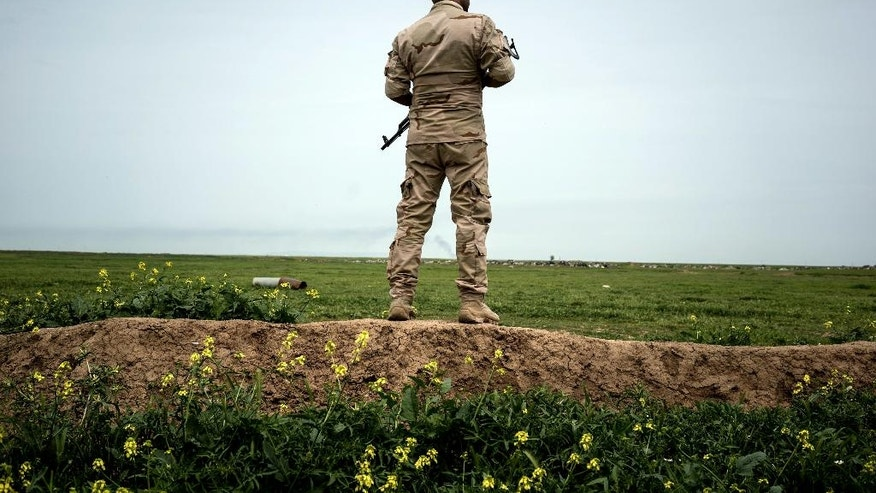 In this April 9, 2016 photo, a soldier part of the Shammar tribal militia stands guard on the border with Syria, in Rabia, northwestern Iraq. When Iraqi Kurdish forces retook Rabia last year it was a major advance against the Islamic State group, which had swept across northern and western Iraq in the summer of 2014 and declared its caliphate across its territory in Iraq and Syria. Now 18 months later, the town demonstrates the difficulties of returning to the way things were before the IS rampage. (AP Photo/Alice Martins)