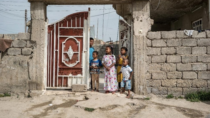 In this April 9, 2016 photo, children stand at the entrance of their home in Rabia, northwestern Iraq. When Iraqi Kurdish forces retook Rabia last year it was a major advance against the Islamic State group, which had swept across northern and western Iraq in the summer of 2014 and declared its caliphate across its territory in Iraq and Syria. Now 18 months later, the town demonstrates the difficulties of returning to the way things were before the IS rampage. (AP Photo/Alice Martins)