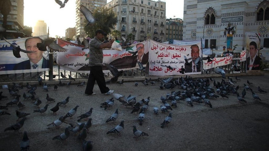 A Syrian man feeds pigeons in front of campaign posters for parliamentary candidates in the Marjeh square, Damascus, Syria, Monday, April 11, 2016. The vote - expected to be a rubber stamp of President Bashar Assad's loyalists - will only proceed in government-controlled areas as the Damascus authorities are unable to organize any balloting in rebel-controlled areas or the territory under the Islamic State group. (AP Photo/Hassan Ammar)