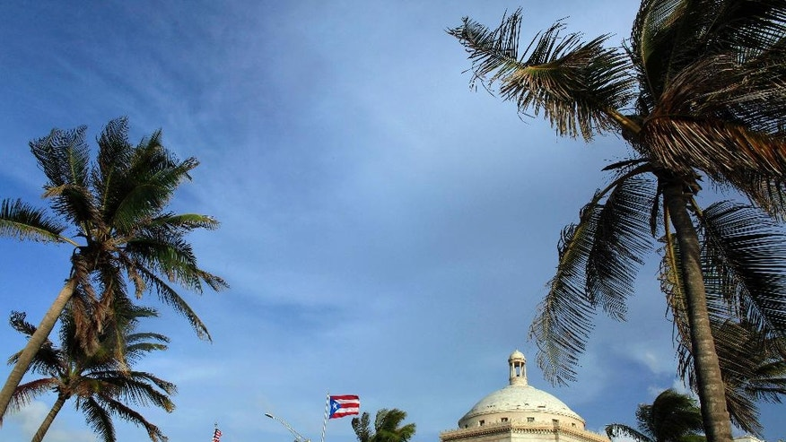 In this July 29, 2015, file photo, U.S. and Puerto Rican flags fly in front of Puerto Rico's Capitol as in San Juan, Puerto Rico. As Puerto Rico teeters on the brink of insolvency, the The Roman Catholic Archdiocese of San Juan has told several hundred current and retired teachers that their pensions have been dispensed with because payouts exceeded contributions. The island has no law overseeing private pensions and it's unclear if the archdiocese's fund was insured. (AP Photo/Ricardo Arduengo, File)
