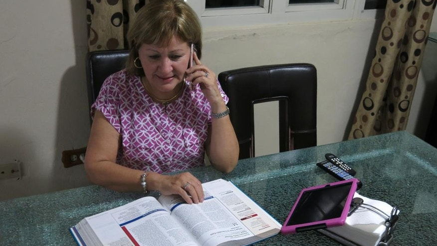 In this March 31, 2016 photo, Catholic school teacher Norma Cardoza talks on her mobile phone to another teacher about losing her pension, in Guaynabo, Puerto Rico. The Roman Catholic Archdiocese of San Juan says the economic crisis has forced so many families to flee Puerto Rico that it is running out of money and has to eliminate pensions, leaving several hundred teachers like Cardoza to face an uncertain future. (AP Photo/Danica Coto)