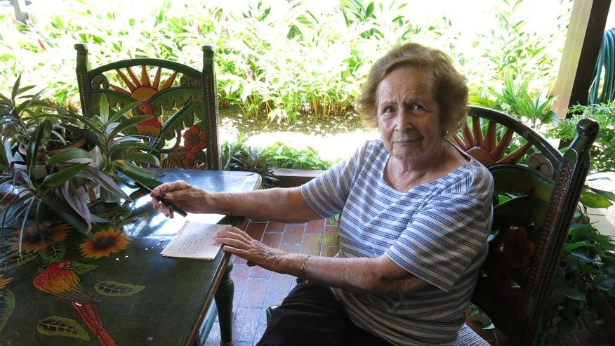 In this April 6, 2016 photo, former Catholic school director and teacher Isabel Casanas talks about losing her pension, in Guaynabo, Puerto Rico. The Roman Catholic Archdiocese of San Juan says the economic crisis has forced so many families to flee Puerto Rico that it is running out of money and has to eliminate pensions, leaving several hundred teachers like Casanas to face an uncertain future. (AP Photo/Danica Coto)