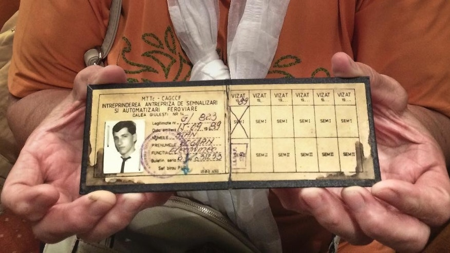 Elene Bancila holds the work id card of her son Bogdan Stan, a 21-year-old rugby player who was fatally shot at the national television station on Dec. 22, 1989, in Bucharest, Romania.  On Tuesday, April 12, 2016, the European Court of Human Rights in Strasbourg ordered Romania to pay compensation to the families of 45 people including Bogdan Stanm, who died during the country's 1989 anti-communist uprising, saying in its ruling that the plaintiffs should each receive 15,000 euros (dlrs 17,300 US). (AP Photo/Alison Mutler)