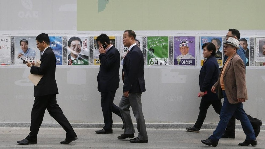People pass by election posters of candidates running for the upcoming parliamentary election in Seoul, South Korea, Tuesday, April 12, 2016. The nation goes to the polls on April 13 to elect members to the 300-seat parliament for a four-year term. (AP Photo/Ahn Young-joon)