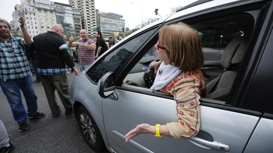 A woman complain as taxi drivers block one of the main avenues in Buenos Aires, Argentina,  Tuesday, April 12, 2016. Hundreds of taxi drivers paralyzed parts of the capital during rush hour to protest Uber launching its service on Tuesday in defiance of local authorities. (AP Photo/Victor R. Caivano)