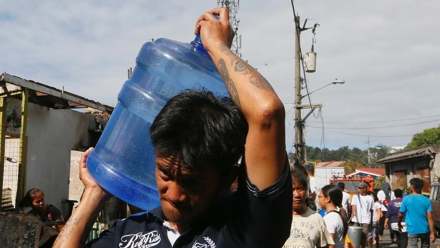 """In this Feb. 23, 2016 photo, a resident carries drinking water following an overnight fire at a poor neighborhood in Muntinlupa city southeast of Manila, Philippines. Water was not supposed to become so expensive for Manila under a 1997 World Bank deal that privatized the seaside city's water and sewage management. That arrangement is under fire by the U.S. congressional committee that oversees the international development bank, which is now questioning whether the World Bank and its lending arm, the International Finance Corp., should join in such """"public-private partnerships.""""  (AP Photo/Bullit Marquez)"""