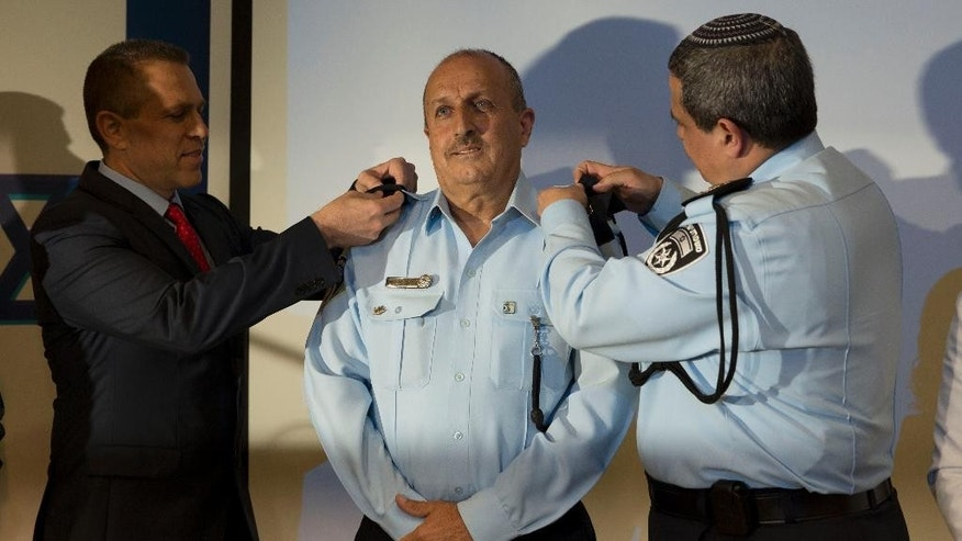 Israeli Public Security Minister Gilad Erdan, left, and Police Chief Roni Alsheikh, right, change the epaulets of newly-named Israeli police deputy commissioner Gamal Hakroosh.