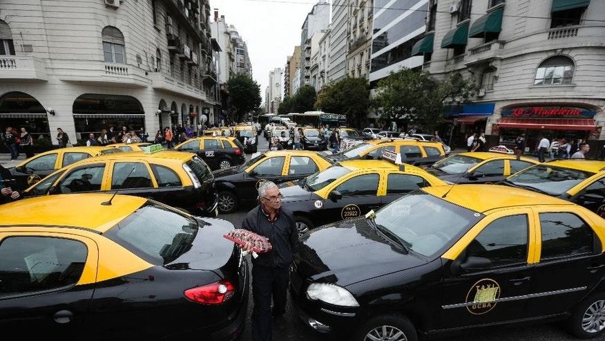 A vendor of caramel-coated peanuts walks among taxis parked in the middle of one of the main avenues of Buenos Aires, Argentina, Tuesday, April 12, 2016. Hundreds of taxi drivers paralyzed parts of the capital during rush hour to protest Uber launching its service on Tuesday in defiance of local authorities. (AP Photo/Victor R. Caivano)