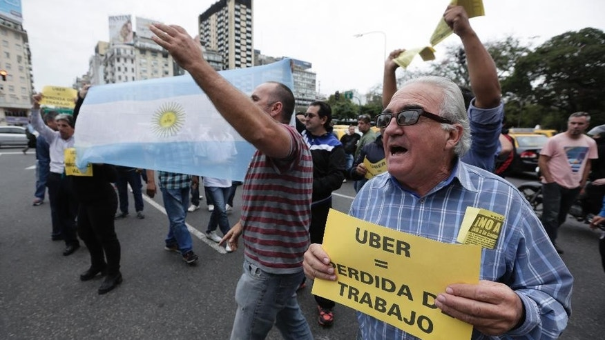 "A taxi driver holds a sign that says in Spanish ""Uber equals job loss"" as he and other cabbies block a main avenue in Buenos Aires, Argentina, Tuesday, April 12, 2016. Hundreds of taxi drivers paralyzed parts of the capital during rush hour to protest Uber launching its service on Tuesday in defiance of local authorities. (AP Photo/Victor R. Caivano)"