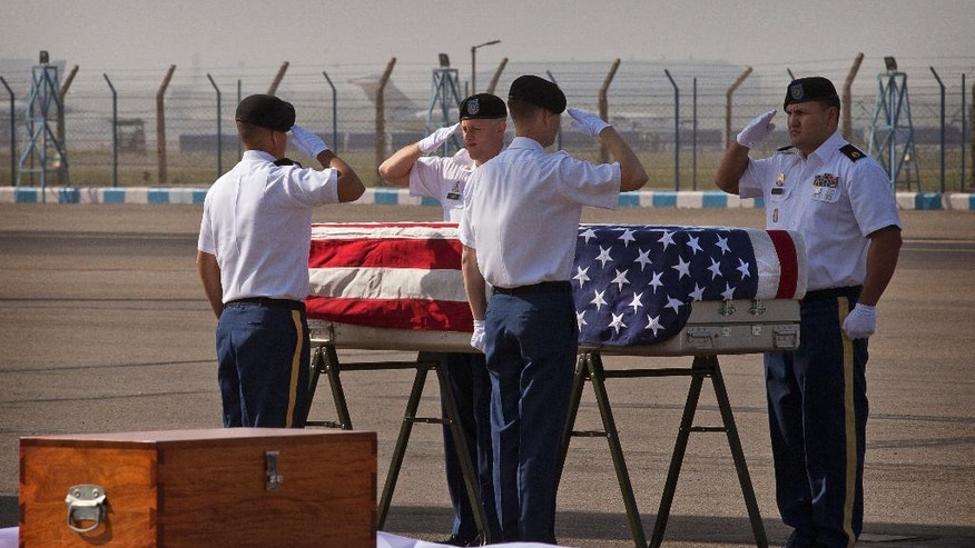 U.S. military members pay final respects to what they believe may be the remains of one to two crew members from a B-24 bomber that crashed during World War II at a ceremony at the Palam airport, in New Delhi, India, Wednesday, April 13, 2016. The bomber was on a supply run from India to China over the Himalayan Mountains when it went missing in 1944. The return of the remains to the U.S. represents the first repatriation of WWII-era remains from India. (AP Photo/Manish Swarup)