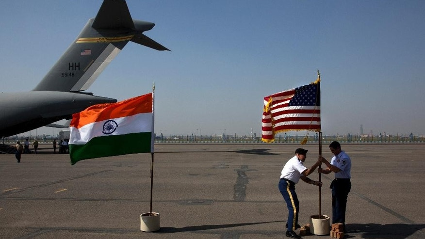U.S. military members remove their flag after a ceremony to pay respects to what they believe may be the remains of one to two crew members from a B-24 bomber that crashed during World War II at the Palam airport, in New Delhi, India, Wednesday, April 13, 2016. The bomber was on a supply run from India to China over the Himalayan Mountains when it went missing in 1944. The return of the remains to the U.S. represents the first repatriation of WWII-era remains from India. (AP Photo/Manish Swarup)