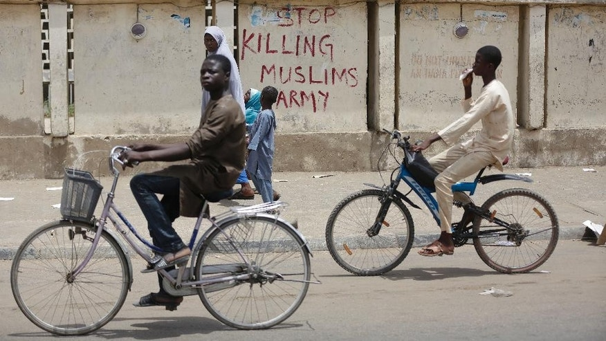 "In this photo taken Friday, April 8, 2016, two boys ride a bicycle past a sign reading ""Stop killing Muslims Army"" on the walls in Kano, Nigeria. Nigeria's Kaduna state government has said it secretly buried hundreds of minority Shiite Muslims in a mass grave, after the victims were killed in army raids that underline ongoing impunity despite President Muhammadu Buhari's promises to end military abuses. Amnesty International is calling for an investigation following what it called ""horrific revelations of the slaughter and secret burial.""(AP Photo/Sunday Alamba)"