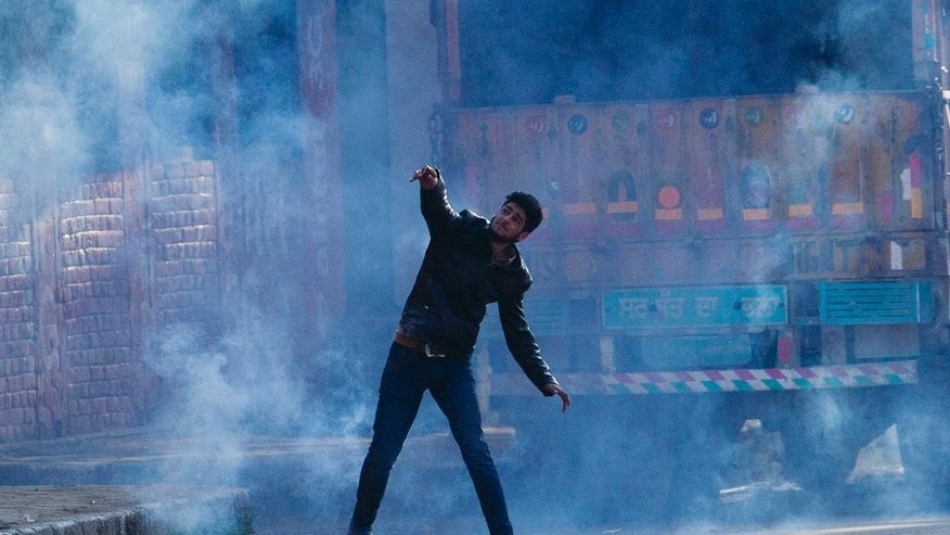 A Kashmiri Muslim protester throws back an exploded tear gas shell at Indian policemen during a protest in Srinagar, Indian controlled Kashmir, Tuesday, April 12, 2016. Two young men were killed in firing by Indian government forces at rock-throwing protesters in the town of Handwara around 80 kilometers (50 miles) north of here on Tuesday, police said. (AP Photo/Dar Yasin)