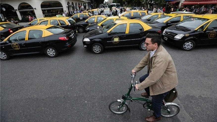 A man rides his bicycle past taxis blocking an avenue in Buenos Aires, Argentina, on April 12, 2016.