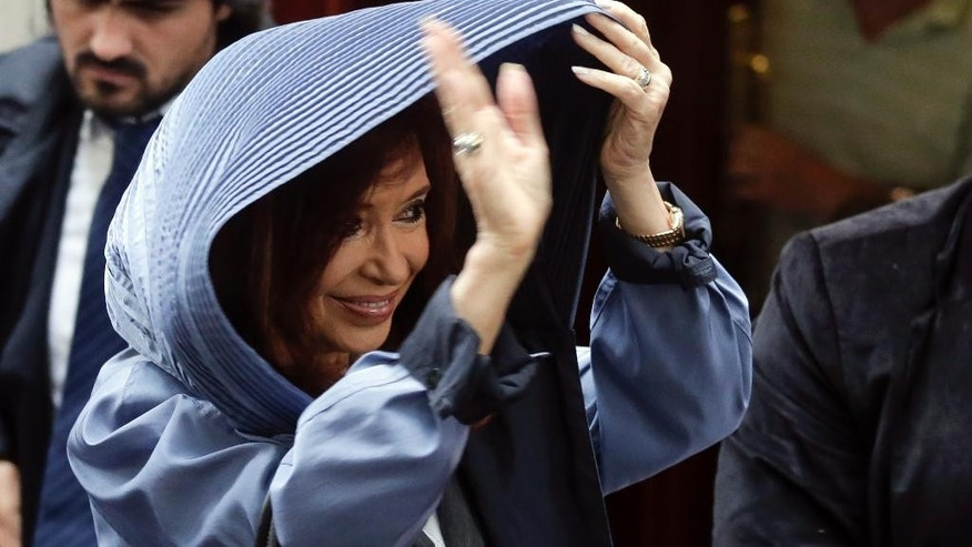 Argentina's former President Cristina Fernandez shades herself from the rain and waves to supporters as she leaves her apartment before heading to court in Buenos Aires, Argentina, Wednesday, April 13, 2016. Fernandez has been called to testify Wednesday in an alleged scheme to manipulate Argentina's currency, marking the first time she has been legally summoned in an investigation against her. (AP Photo/Victor R. Caivano)