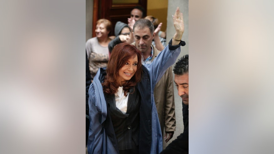 Argentina's former President Cristina Fernandez waves to supporters from outside her apartment before heading to court in Buenos Aires, Argentina, Wednesday, April 13, 2016. Fernandez has been called to testify Wednesday in an alleged scheme to manipulate Argentina's currency, marking the first time she has been legally summoned in an investigation against her. (AP Photo/Victor R. Caivano)