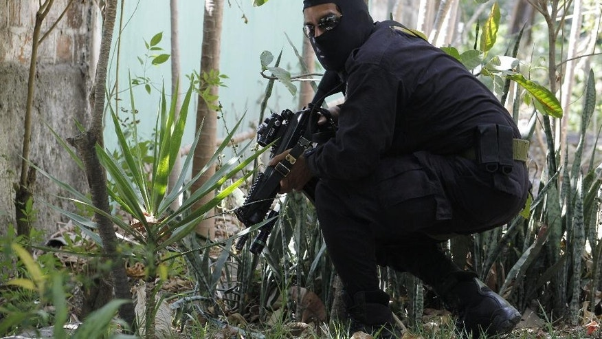In this April 5, 2016 photo, a masked and armed policeman crouches as he patrols a gang controlled neighborhood in San Salvador, El Salvador. Hyper-violent gangs declared open-season on police in this Central American nation in response to a government crackdown that began last year. Gangs set up training camps in the mountains and unleashed car bombs in the capital. They adopted no-holds-barred tactics targeting police and their loved ones, as well as the army as soldiers become more involved in the fight. (AP Photo/Alex Peña)