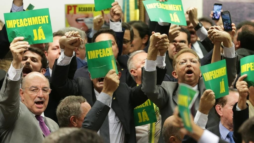 "As they hold a sign reading ""impeachment now"" opposition lawmakers celebrate after the results of the voting at a congressional committee in Brasilia, Brazil , Monday, April 11, 2016. The committee voted Monday to recommend that the impeachment process against President Dilma Rousseff move forward, bringing the possible ouster of the embattled leader a step closer.(AP Photo/Eraldo Peres)"