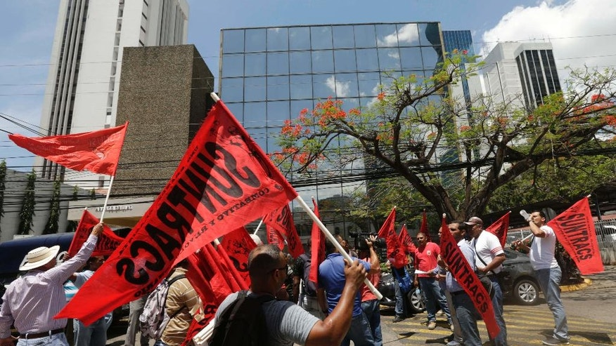 Construction workers protest outside the Mossack Fonseca law firm, demanding the government punish anyone involved in financial crimes in Panama City, Wednesday, April 13, 2016. Organized crime prosecutors raided the offices of the Mossack Fonseca law firm on Tuesday, which continued into Wednesday, looking for evidence of money laundering and financing terrorism following a leak of documents about tax havens it set up for wealthy international clients. (AP Photo/Arnulfo Franco)