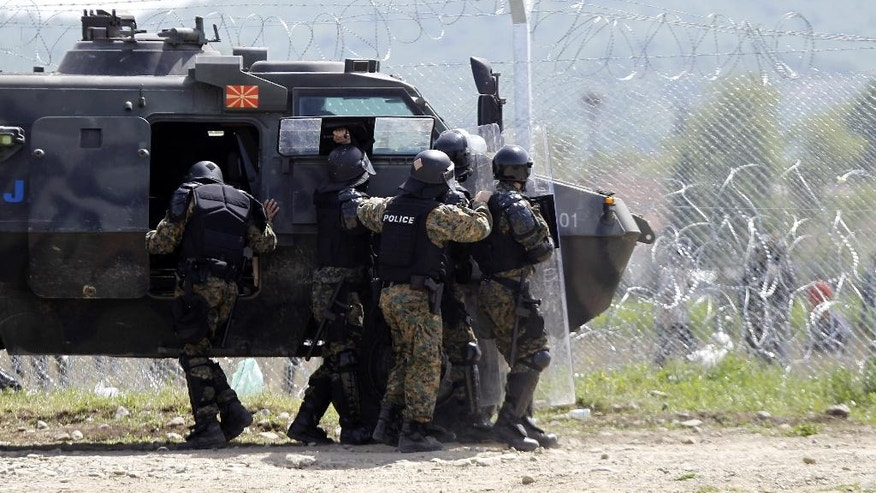 """Macedonian police officers try to protect themselves from the rocks thrown by migrants from the Greek side of the border fence between Macedonia and Greece, near southern Macedonian town of Gevgelija, Wednesday, April 13, 2016. The presidents of Macedonia, Croatia and Slovenia were to visit the provisional migrant's checkpoint known as """"Stone 59"""" on Macedonia's border with Greece, but President's tour was canceled at last moment due to security reasons as about 300 migrants from the Greek side have tried to break the fence. (AP Photo/Boris Grdanoski)"""