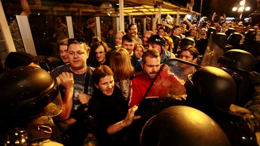 Protestors scuffle with the police in downtown Skopje, Macedonia, Tuesday, April 12, 2016. Several hundred people protested late Tuesday outside the offices of the ruling conservative VMRO-DPMNE party and in front of President Ivanov office in downtown Skopje, throwing eggs and demanding his resignation. Macedonian President Gjorge Ivanov has announced earlier Tuesday he is granting a presidential pardon terminating all criminal proceedings against politicians from both the ruling parties and the opposition. (AP Photo/Boris Grdanoski)
