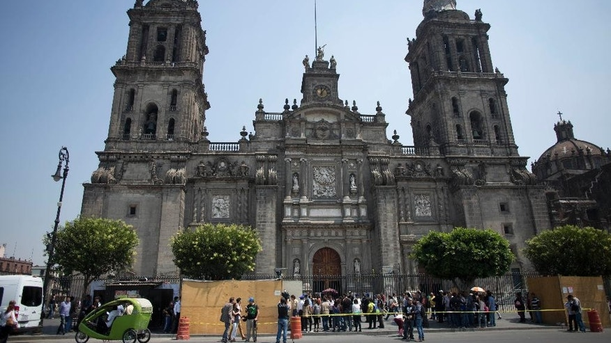 Reporters stand near the site where archeologists found a massive stone slab near the Cathedral in Mexico City, Wednesday, April 13, 2016. Archaeologists found a massive stone slab covering the tomb of one of the first priests in Mexico following the 1521 European conquest, a grave sunk into the floor of what appears to be an Aztec temple. (AP Photo/Eduardo Verdugo)