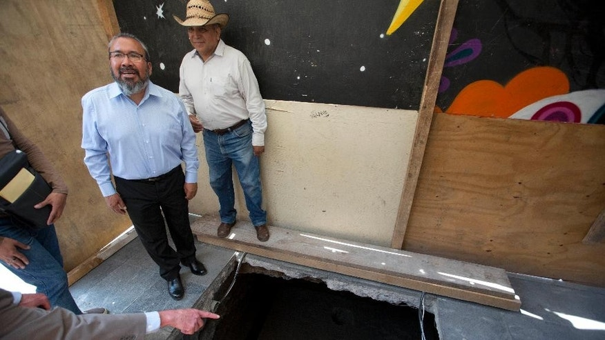 Archaeologist Raul Barrera, of the National Institute of Anthropology and History, left, talks with the press at the site where a massive stone slab was discovered on the sidewalk in front of the Cathedral in Mexico City, Wednesday, April 13, 2016. Archaeologists have found a massive stone slab covering the tomb of one of the first priests in Mexico following the 1521 European conquest, a grave sunk into the floor of what appears to be an Aztec temple. (AP Photo/Eduardo Verdugo)