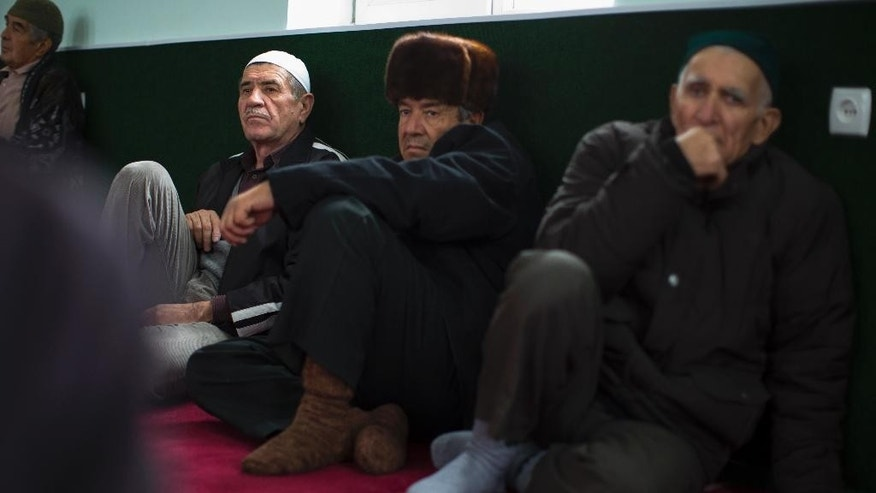 FILE  In this file photo taken on Friday, Oct.  24, 2014, Crimea Tatar men wait for the beginning of Friday's prayer inside a mosque in Sary-Su, Crimea. The chief prosecutor of Crimea has ordered a suspension of the council representing the region's Tatar ethnic minority. Tatars make up about 15 percent of the region's nearly 2 million people and have been broadly opposed to Russia's annexation of the peninsula from Ukraine in 2014. (AP Photo/Alexander Zemlianichenko, file)