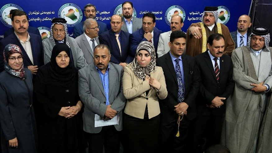 Lawmakers, who held a sit-in overnight inside the parliament building, stand during a news conference, in Baghdad, Iraq, Wednesday, April 13, 2016. For the second consecutive day, at least one hundred lawmakers from Shiite and Sunnis, have continued holding a sit-in inside the hall of meetings of the parliament, protesting at the postponement of vote on the technocrat cabinet. (AP Photo/Karim Kadim)