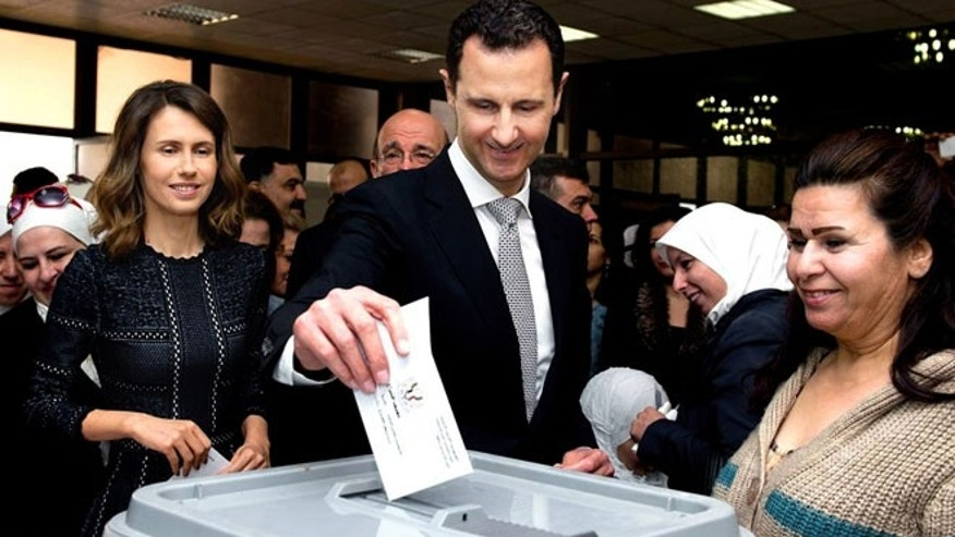APRIL 13: This photo released on the official Facebook page of Syrian Presidency, shows Syrian President Bashar Assad casting his ballot in the parliamentary elections, as his wife Asma, left, is standing next to him, in Damascus.
