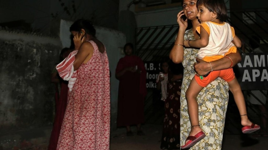 Resident women who rushed outdoors following tremors speak on their mobile phones outside their houses in Kolkata, India, Wednesday, April 13, 2016. A strong earthquake struck Myanmar on Wednesday night and was felt in parts of eastern India and Bangladesh, causing residents to rush out of their homes in panic. There were no immediate reports of injuries or damage.(AP Photo/Bikas Das)