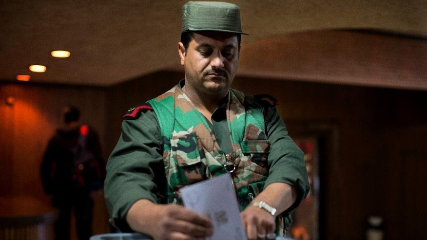 A Syrian policeman casts his vote at a polling station during the parliamentary election in Damascus, Syria, Wednesday, April 13, 2016. Polling stations opened in government-held parts of Syria where a new 250-member parliament will be elected. (AP Photo/Hassan Ammar)