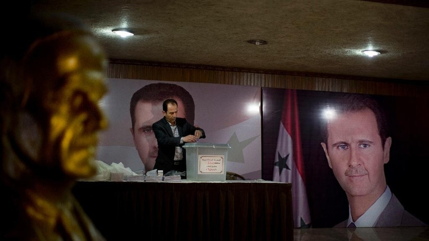 A Syrian election official waits for voters at a polling station with posters of President Bashar Assad during the parliamentary election in Damascus, Syria, Wednesday, April 13, 2016. Polling stations opened in government-held parts of Syria where a new 250-member parliament will be elected. (AP Photo/Hassan Ammar)