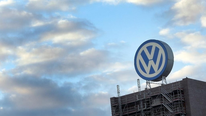 FILE - In this Sept. 26, 2015 file photo a giant logo of the German car manufacturer Volkswagen is pictured on top of a company's factory building in Wolfsburg, Germany. Volkswagen says its managers' bonuses will be cut following the automaker's diesel emissions scandal. The automaker said in a statement Wednesday April 13, 2016  managers and directors agree that the company has to send a signal regarding the management board's pay in light of the current situation.  (AP Photo/Michael Sohn, file)