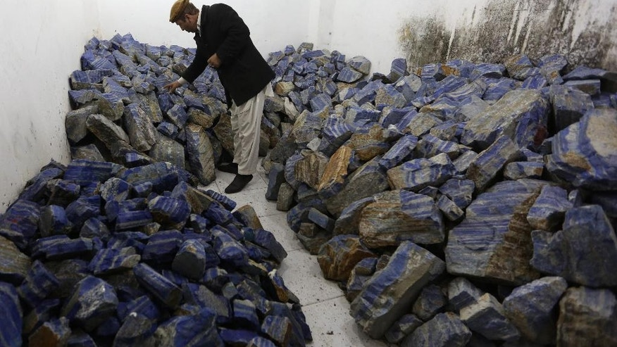 In this Monday, March 28, 2016 photo, an Afghan businessman checks lapis lazuli at his shop in the city of Kabul, Afghanistan. The brilliant blue stone lapis lazuli, prized for millennia, is almost uniquely found in Afghanistan, a key part of the extensive mineral wealth that is seen as the best hope for funding development of one of the world's poorest nations. (AP Photo/Rahmat Gul)
