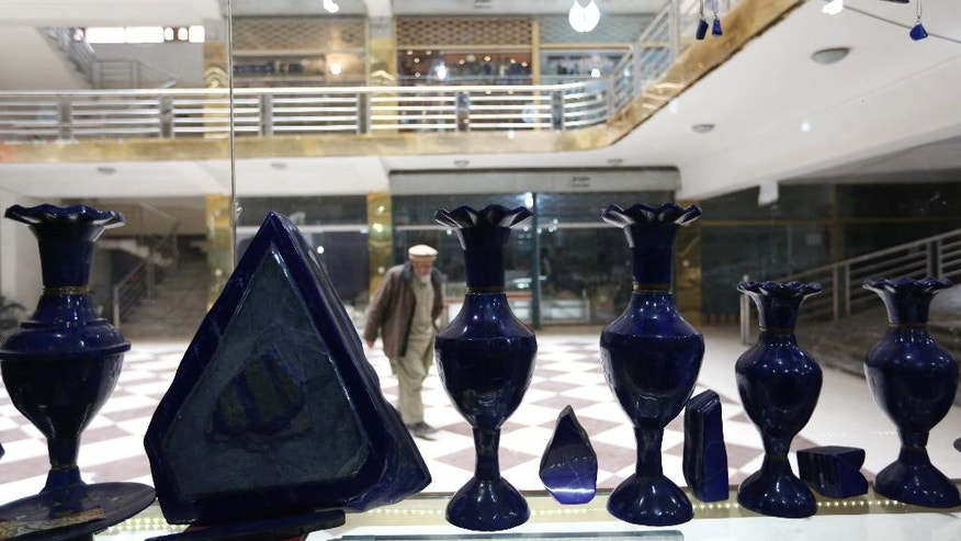 In this Monday, March 28, 2016 photo, an Afghan man walks in front of a lapis lazuli shop in the city of Kabul, Afghanistan. The brilliant blue stone lapis lazuli, prized for millennia, is almost uniquely found in Afghanistan, a key part of the extensive mineral wealth that is seen as the best hope for funding development of one of the world's poorest nations. (AP Photo/Rahmat Gul)