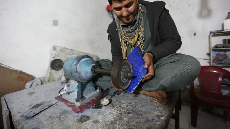 In this Monday, March 28, 2016 photo, an Afghan man works at a lapis lazuli factory in the city of Kabul, Afghanistan. The brilliant blue stone lapis lazuli, prized for millennia, is almost uniquely found in Afghanistan, a key part of the extensive mineral wealth that is seen as the best hope for funding development of one of the world's poorest nations. (AP Photo/Rahmat Gul)