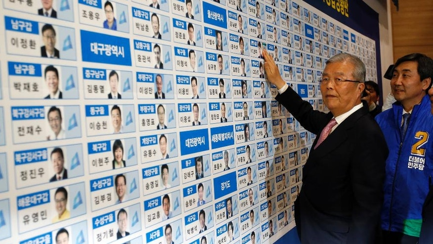 Kim Chong In, a chairman of the main opposition party, the Minjoo Party of Korea, looks at the cameras as he places a sticker onto one of the party's winning candidates' photographs for parliamentary election in Seoul, South Korea, Wednesday, April 13, 2016.  South Koreans voted in parliamentary elections Wednesday that were expected to hand a decisive win to President Park Geun-hye's conservative party, and enable her to push ahead with controversial economic reforms. Exit polls, however, indicated her party would not regain its majority in the National Assembly. (AP Photo/Lee Jin-man, Pool)