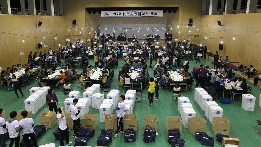 South Korean National Election Commission officials sort out ballots in the country's parliamentary elections as they begin the counting process in Seoul, South Korea, Wednesday, April 13, 2016. President Park Geun-hye's conservative party seemed headed for a shocking setback after South Koreans voted in parliamentary elections on Wednesday, with early vote counts suggesting it would not regain its majority in the National Assembly. (AP Photo/Ahn Young-joon)