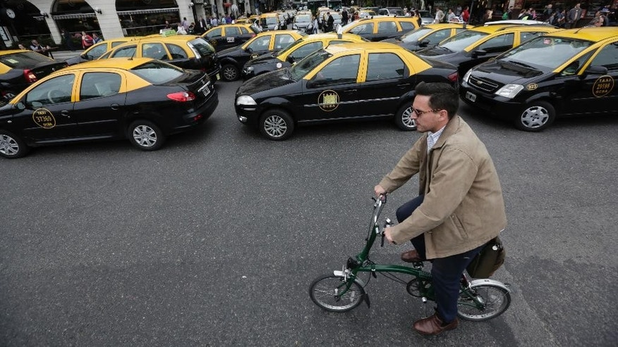 A man rides his bicycle past taxis blocking a main avenue in Buenos Aires, Argentina, Tuesday, April 12, 2016. Hundreds of taxi drivers paralyzed parts of the capital during rush hour to protest Uber launching its service on Tuesday in defiance of local authorities. (AP Photo/Victor R. Caivano)