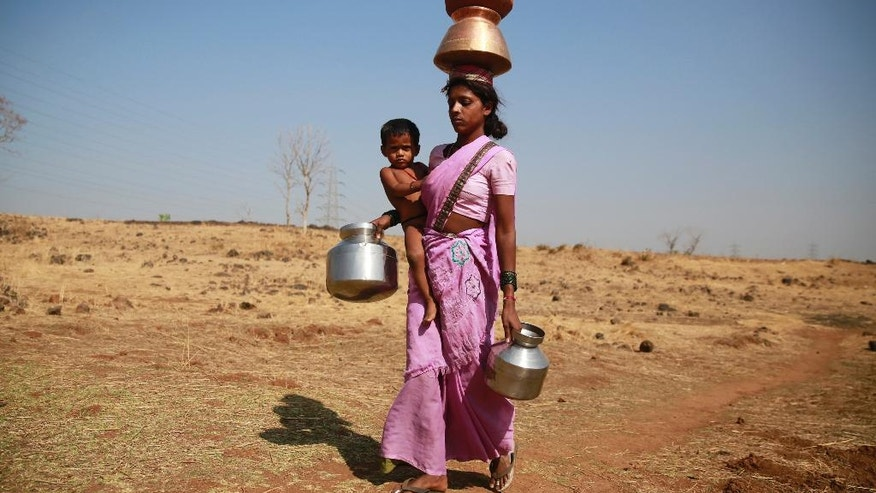 In this April 12, 2016 photo, a woman along with her son walks to get water from a communal tube well at Raichi Wadi village, 120 kilometers (75 miles) north-east of Mumbai, India. Decades of groundwater abuse, populist water policies and poor monsoons have turned vast swaths of central and western India into a dust bowl, driving distressed farmers to suicide or menial day labor in the cities. (AP Photo/Rafiq Maqbool)