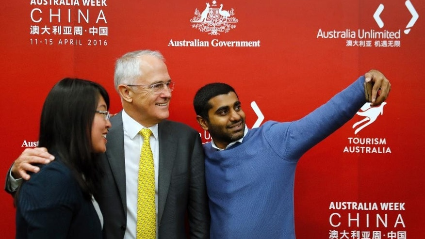 Australian Prime Minister Malcolm Turnbull, center, poses for a selfie with delegates from Australia and China during an event at the Shanghai International Expo Center in Shanghai, China, Thursday, April 14, 2016. (AP Photo/Andy Wong)