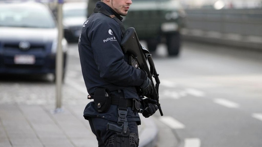 A police officer patrols outside the federal court building in Brussels on Thursday, April 14, 2016. Suspects from the Brussels and Paris attacks appeared in court Thursday for a court hearing to decide whether or not to extend their detention. (AP Photo/Virginia Mayo)