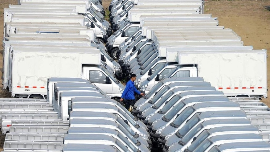 A man walks between vehicles in the parking lot of a refitting factory in Qingdao in east China's Shandong province Friday, April 15, 2016. China's economic growth slowed in the first quarter to 6.7 percent compared with the previous year, according to official data released Friday, April 15, 2016. (Chinatopix Via AP) CHINA OUT