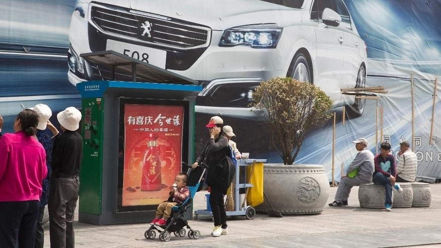 In this Wednesday, April 13, 2016 photo, a child eats ice cream as he is pushed past a car advertisement in Beijing. China's economic growth slowed in the first quarter to 6.7 percent compared with the previous year, according to official data released Friday, April 15, 2016. (AP Photo/Ng Han Guan)