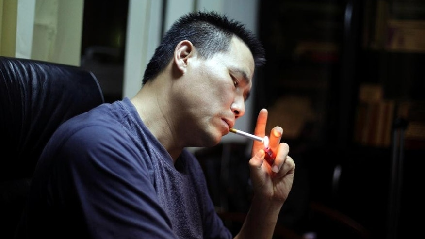 In this June 30, 2010 file photo, Prominent Chinese human rights lawyer Pu Zhiqiang  lights a cigarette during an interview at his office in Beijing. Pu posted a notice on his microblog on Thursday, April 14, 2016 that he has been disbarred, a further step in what the U.S. State Department and rights groups call a relentless crackdown by Beijing on efforts to establish an independent rule of law. (AP Photo/Ng Han Guan, File)