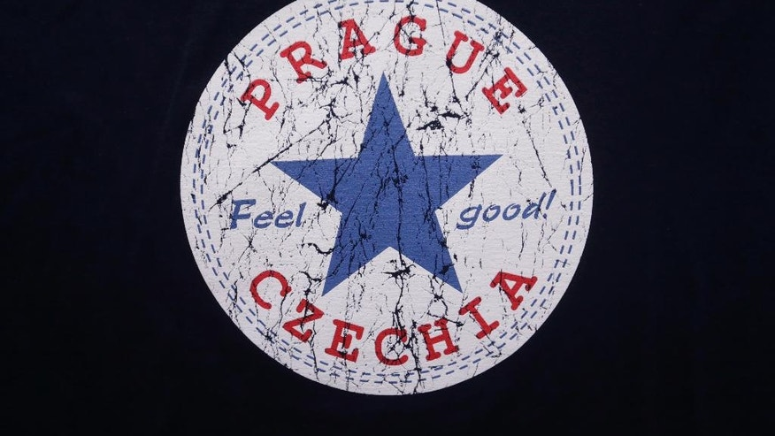 "A sign with the word ""Czechia"" is printed on a t-shirt displayed in a store in Prague, Czech Republic, Thursday, April 14, 2016. Feeling as a handicap that unlike most European countries the Czech Republic lacks a one-word version of its name in foreign languages, the country is set to use the name of Czechia in English. (AP Photo/Petr David Josek)"
