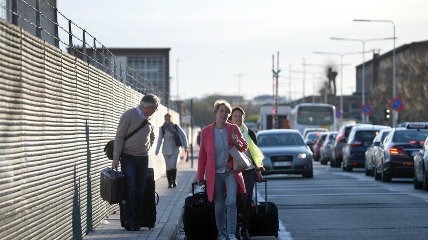 Passengers walk with their luggage on the main road to Zaventem Airport in Brussels on Tuesday, April 12, 2016. A wildcat strike of air traffic controllers has paralyzed Brussels airport after their guild rejected a compromise aimed at solving a conflict over a pension reform. The strike action comes at a time when traffic was already reduced at the airport in the wake of the March 22 attacks. (AP Photo/Virginia Mayo)