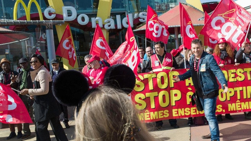Unionists and fast food workers demonstrate outside the McDonald's fast food restaurant at the Disneyland Paris theme park, in Marne la Vallee, outside Paris, Thursday, April 14, 2016. In the United States, protesters calling for pay of $15 an hour are expected to hold demonstrations at McDonald's stores around the country Thursday. McDonald's said it gives American workers access to a program that helps them with education and is raising starting wages. (AP Photo/Thibault Camus)