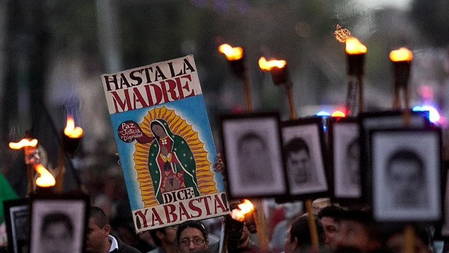 FILE - In this Dec. 26, 2015, file photo, relatives of the 43 missing students from the Isidro Burgos rural teachers' college march and hold pictures of their missing loved ones during a protest in Mexico City. Mexico's national human rights commission said Thursday, April 14, 2016, that it had found a witness to the 2014 disappearance of the college students who reported that federal and municipal police were present when the youths were taken off a bus and disappeared. (AP Photo/Marco Ugarte, File)
